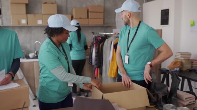 인도주의 적 지원을 포장하는 자원 봉사자 - giving tuesday 스톡 비디오 및 b-롤 화면
