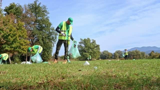 Volunteers picking up litter in a sunny meadow in a local clean-up event