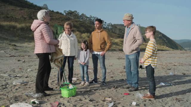 vidéos et rushes de volontaires se préparant à nettoyer la plage - expliquer