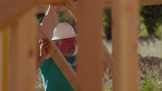 frivilliga höja väggen på byggprojekt - välgörenhet bildbanksvideor och videomaterial från bakom kulisserna