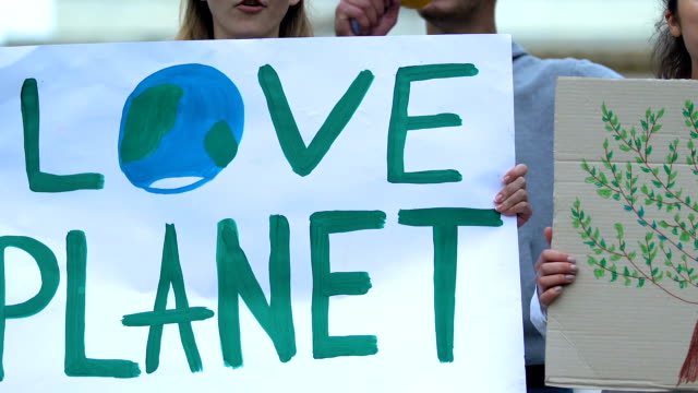 Volunteers showing Love planet slogan, ecological extinction, deforestation