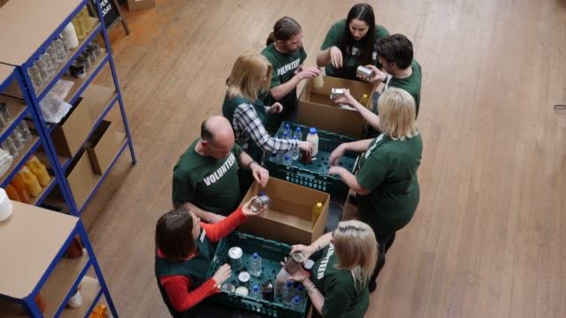 4k antenn: volontärer sortering mat i lådor i en food bank - välgörenhet bildbanksvideor och videomaterial från bakom kulisserna