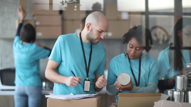 기부 상자를 작업, 확인 및 포장하는 자원 봉사자 - giving tuesday 스톡 비디오 및 b-롤 화면