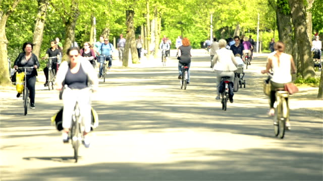 Vondelpark Amsterdam and the cyclists Full HD footage of large group of people are cycling through the Vondelpark in Amsterdam, the Netherlands. Selective focus used with copy space above. amsterdam stock videos & royalty-free footage