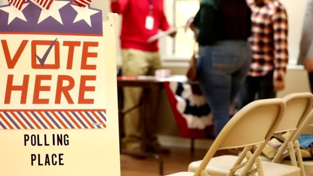 vídeos y material grabado en eventos de stock de vota aquí. los estadounidenses se inscriben para votar en la mesa electoral en las elecciones de estados unidos. - polling place