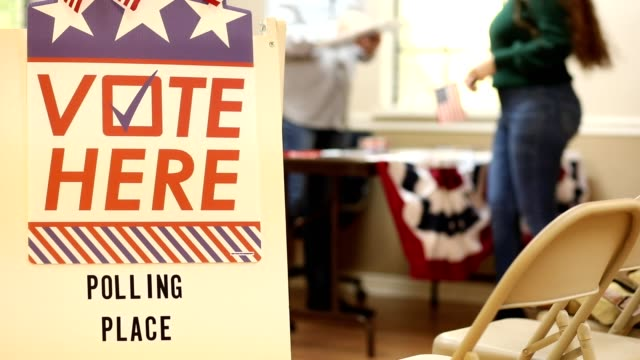 Vote Here. American people register to vote at polling station in USA election. video