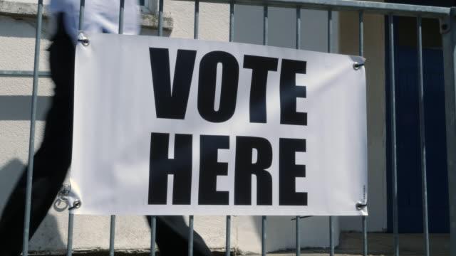 vídeos y material grabado en eventos de stock de 4k: voto aquí firma / banner - gente que va a votar en las elecciones - polling place