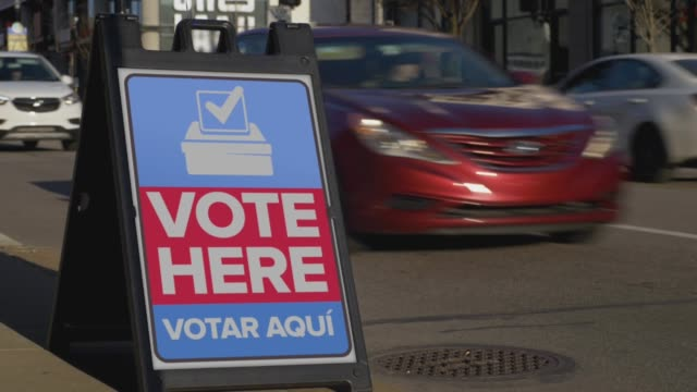 Vote Here Sign on the Sidewalk of a Large City video