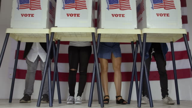 Voters legs standing at booths at polling station video