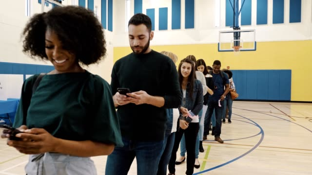 voters use smartphones while waiting in line to vote - in fila video stock e b–roll