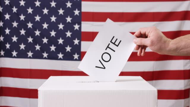 vidéos et rushes de main de vote avec le drapeau américain - picto urne