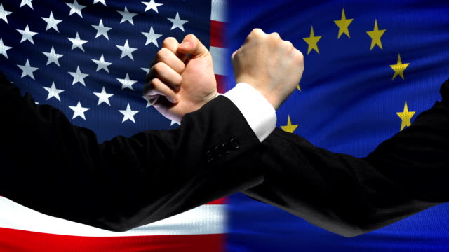 US vs EU confrontation, countries disagreement, fists on flag background