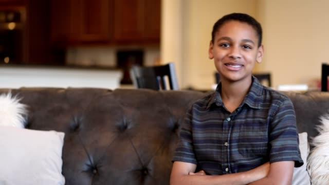 Waist up shot of African descent teenage boy at home. video