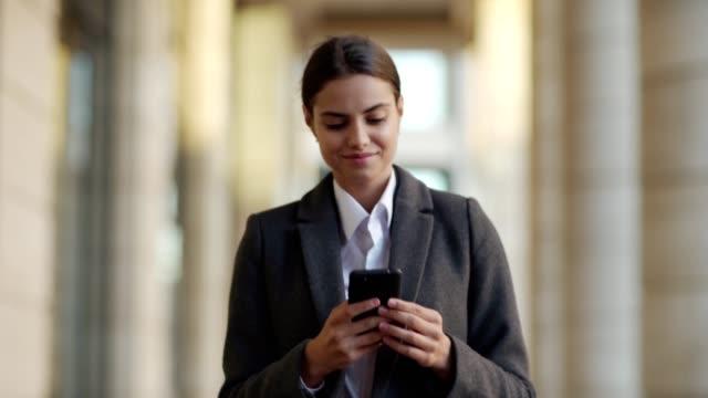vídeos y material grabado en eventos de stock de cintura arriba tiro de atractiva joven en abrigo caminando por la calle después del trabajo. una empresaria sonriente leyendo mensajes de texto en el teléfono celular o navegando por las redes sociales - toma mediana