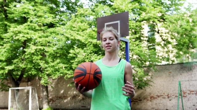 vídeos y material grabado en eventos de stock de cintura arriba tiro a cámara lenta de jugador de baloncesto femenino confiado lanzando la pelota de una mano a otra de pie en la cancha al aire libre y mirando la cámara - rivalidad
