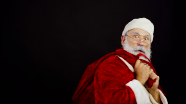 vídeos de stock e filmes b-roll de waist up studio shot of shocked santa claus pulling christmas sack trying to take gifts away from somebody and finally walking away with presents against black background - puxar