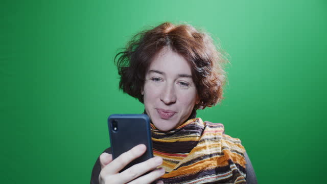 Waist-up portrait of mature woman using her smart phone over green chroma key background video
