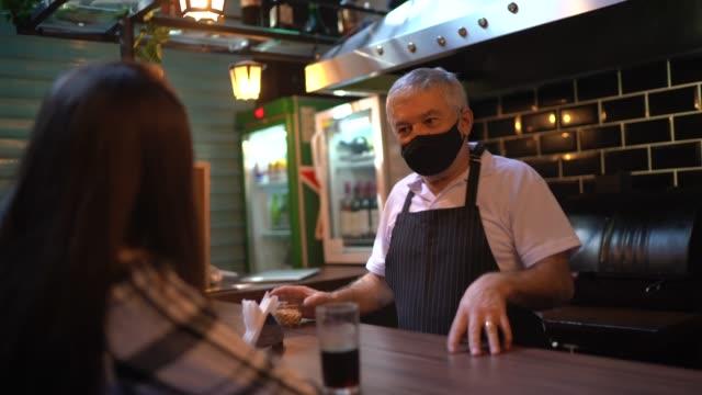 ein kellner hinter dem tresen, der in einem restaurant zum kunden geht - mit gesichtsmaske - bedienungspersonal stock-videos und b-roll-filmmaterial