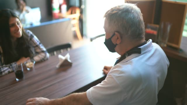 A waiter behind the counter taking to client's in a restaurant - using face mask A waiter behind the counter taking to client's in a restaurant - using face mask wait staff stock videos & royalty-free footage