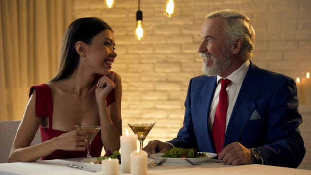 Waiter bringing bill to old millionaire having dinner with young lady, lovers Waiter bringing bill to old millionaire having dinner with young lady, lovers wait staff stock videos & royalty-free footage