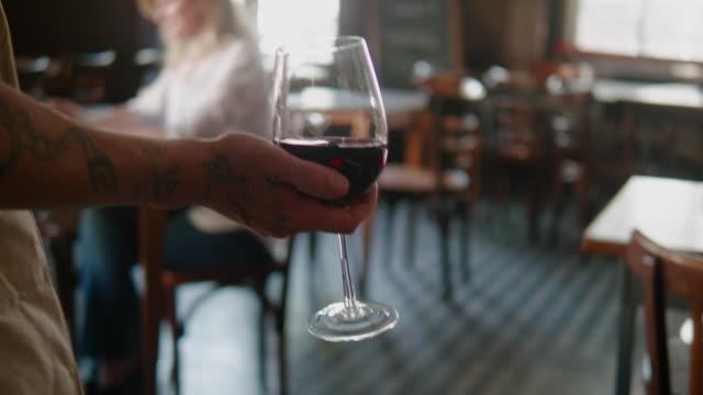 vídeos de stock, filmes e b-roll de empregado de mesa que traz o vinho vermelho ao cliente no restaurante argentino - sul europeu