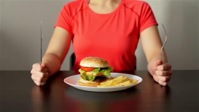 vidéos et rushes de le garçon apporte la nourriture rapide et la nourriture saine à une femme - tentation