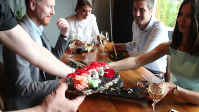 Waiter brings sushi to dining table video