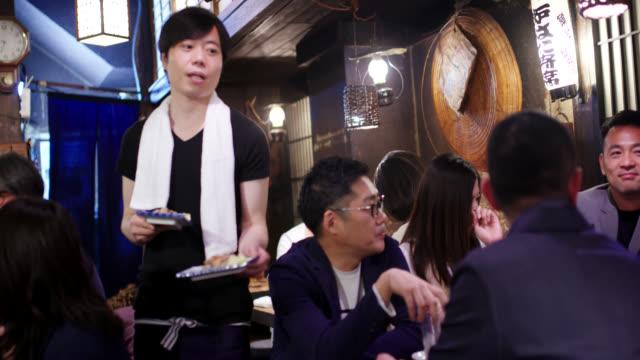 日本の居酒屋で食卓に食べ物を届けるウェイター - 飲食店点の映像素材/bロール