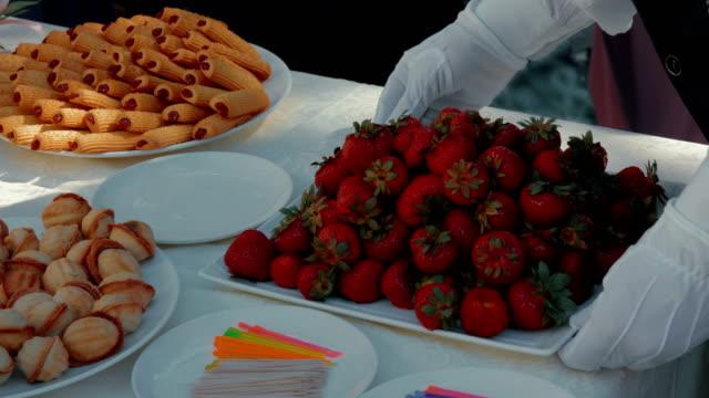 vídeos y material grabado en eventos de stock de camarero en guantes blancos que sirve de mesa para la recepción - comida francesa