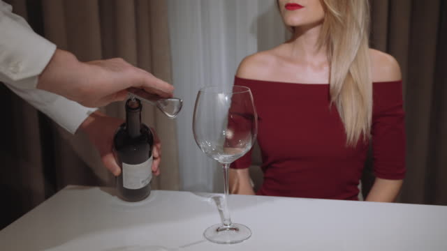 waiter opens a bottle of red wine for a woman in a restaurant video