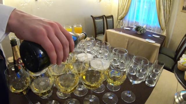 vídeos de stock e filmes b-roll de waiter pours champagne into the glasses - sideboard