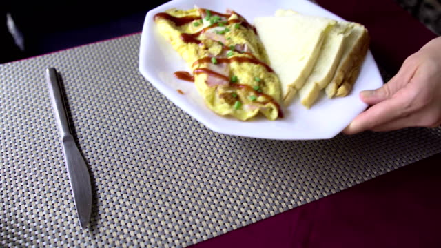Waiter serve omelette with ham and toast on white plate in restaurant. Close-up of waitress serving morning breakfast. video