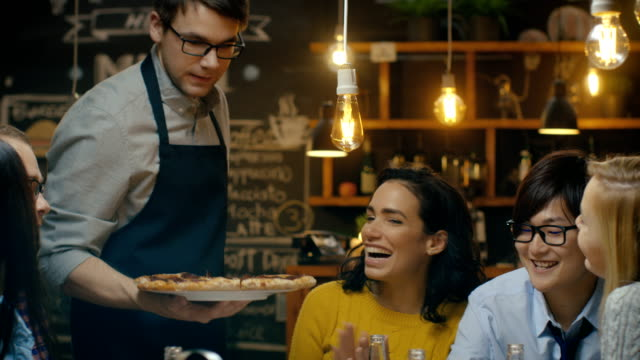 waiter serves delicious pizza to a diverse group of hungry and happy friends. they eat, drink and have fun in this stylish looking bar. - обслуживание стоковые видео и кадры b-roll