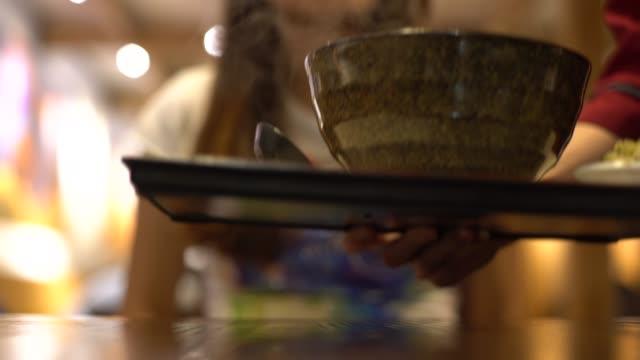 vídeos de stock, filmes e b-roll de o empregado de mesa 4k sere o alimento chinês tradicional quando mulher asiática que usa o smartphone - comida chinesa