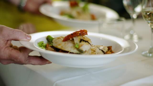 waiter serves two means - fish and vegetables - готовый к употреблению стоковые видео и кадры b-roll