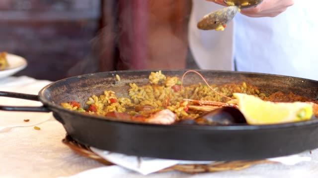 vídeos y material grabado en eventos de stock de un camarero que sirve una tradicional comida de paella mediterránea en el restaurante español - comida española
