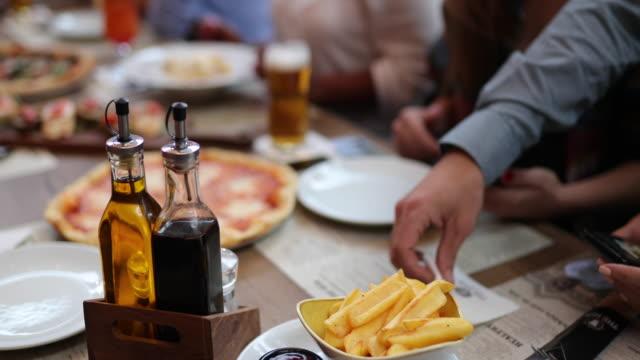 Waiter serving beer to friends at outdoor restaurant