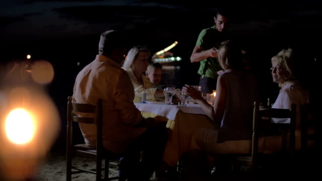 Waiter serving dinner for family in outdoor cafe Family having meal in outdoor restaurant on the beach at night. Waiter serving dinner, burning tiki torch in foreground wait staff stock videos & royalty-free footage