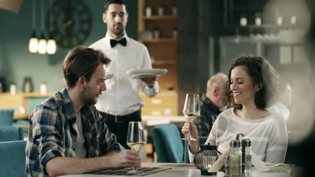 Waiter serving dishes to couple sitting at table in restaurant video