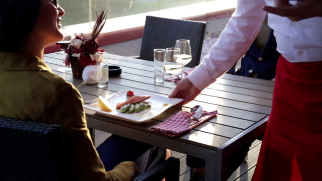 Waiter serving food in outdoor restaurant video