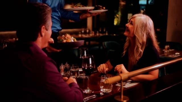 グルメ レストランでエレガントな大人のカップルに料理ウェイター - 老夫婦点の映像素材/bロール