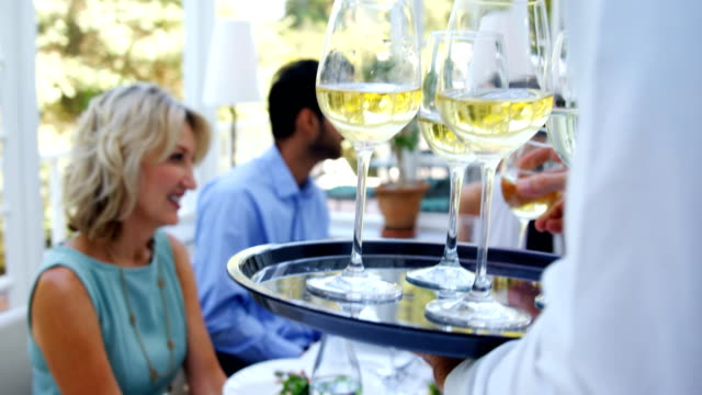 Waiter serving glasses of wine to customer Waiter serving glasses of wine to customer in restaurant tray stock videos & royalty-free footage
