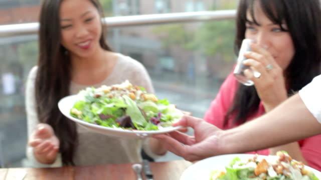 kellner servieren mittagessen und drei freundinnen im restaurant - salat speisen stock-videos und b-roll-filmmaterial