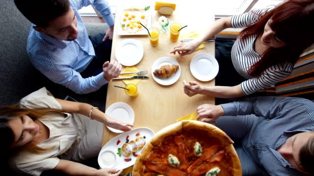 kellner setzt auf dem tisch eine pizza an junge freunde, genießen ein abendessen im restaurant - restaurant stock-videos und b-roll-filmmaterial