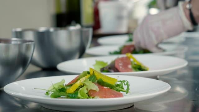 Um empregado de mesa ajusta a tabela em um restaurante antes que os clientes cheguem, e use a cutelaria e os vidros finos. - vídeo