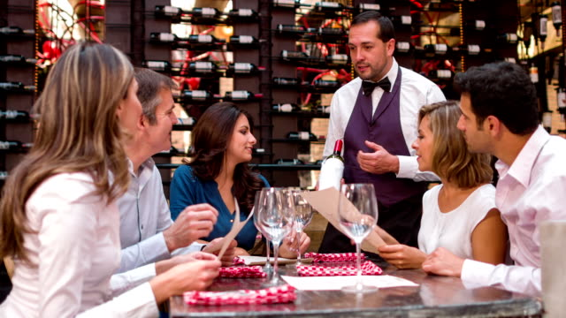 Waiter suggesting a wine to a group of people video