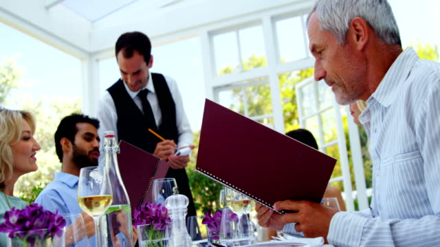 Waiter taking an order from customers Waiter taking an order from customers in restaurant menu stock videos & royalty-free footage