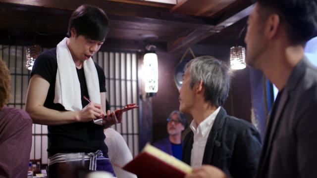 日本式レストランで注文を取るウェイター - 外食産業関係の職業点の映像素材/bロール