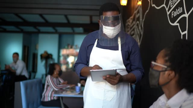 vídeos de stock e filmes b-roll de waiter taking client's order, using a digital tablet in a restaurant - using face mask - covid restaurant