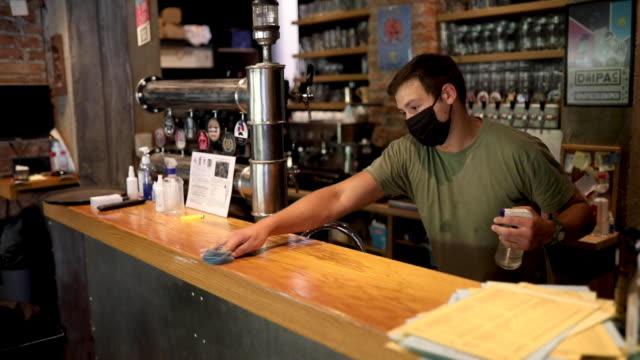 servitör med desinfektion produkt för att rengöra bar disk innan han öppnar bryggeri - bänk bildbanksvideor och videomaterial från bakom kulisserna